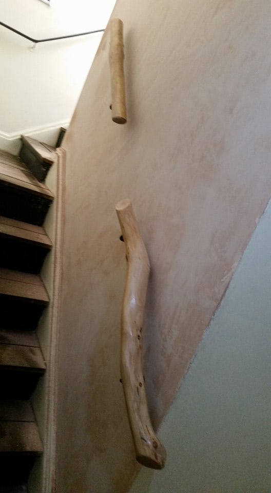 staircase with metal handrail and split wooden handrail with bare wall