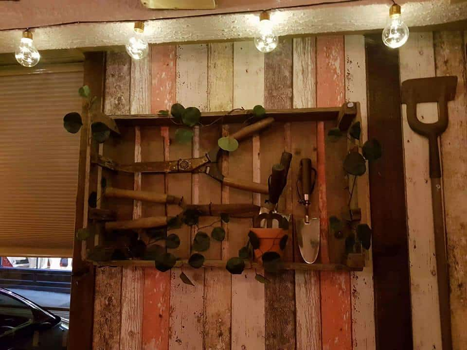 wooden wall in pub with faded paint and display of garden tools